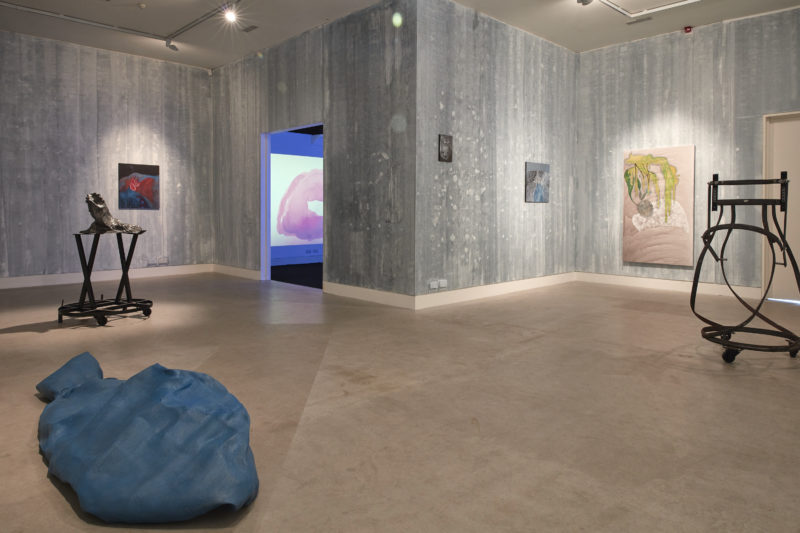An L shaped gallery the walls are painted in a blue-green ink wash that resembles the sea. There are three sculptures on the floor, two are steel structures used in Fani's previous performances and the third is a blue amorphous shape with ripples.