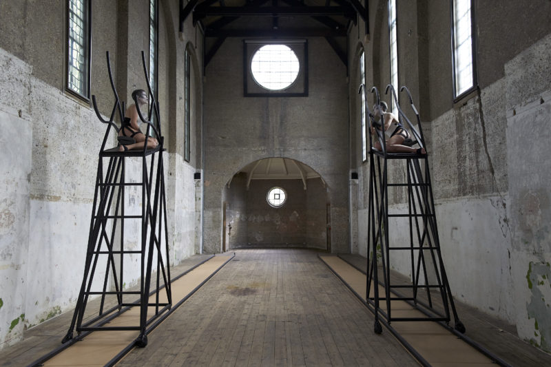 Two large steel platforms on tracks that run parallel to the walls of a deconsecrated church. Two performers are sat on top of the platforms.