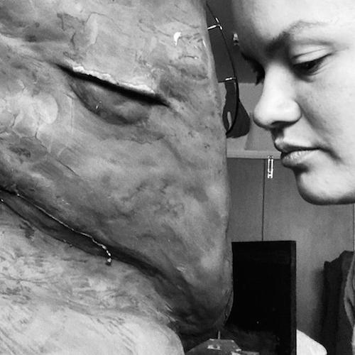 A black and white photograph of artist Fani Parali face to face with her sculpture of a harpy eagle.