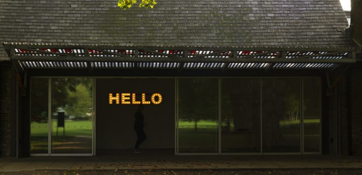 Hello sign illuminated with orange lights framed by the entrance of Southwark Park Galleries // Dilston Gallery. Part of Peter Liversidge's 2012 exhibition As Sculpture