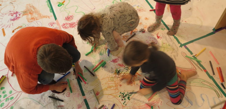 Various children's drawings on paper completely covering the floor for Drawing Disco at Southwark Park Galleries. Two children surrounded by pens are drawing with Alexa Lowe crouched next to them and one child standing.