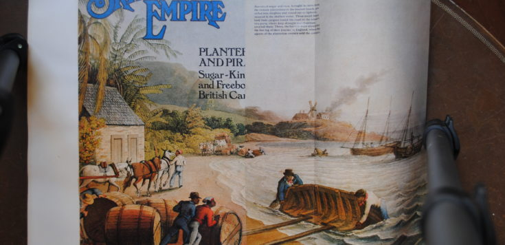 A magazine cutting with the title 'The British Empire' in blue print, in the left-hand corner and a 1823 painted scene of men in Barbados pushing barrels of sugar and rum on the shore, ready to be shipped to England. In the left-hand corner, a paragraph in small print reads: 'Barrels of sugar and rum, brought in carts from the remote plantations to the nearest beach, are rolled in dinghies and rowed out to lighters moored in the shallow water. These small boats took their cargoes round the coast to the island's two ports, where deep-draught merchantmen awaited them. There, the barrels were stowed for the last leg of their journey to England, where the agents of the plantation-owners sold the contents'.