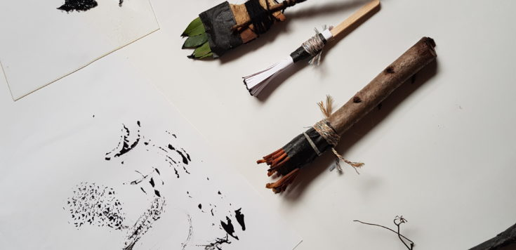 Five paintbrushes laid out one above the other made out of natural materials such as twigs and leaves on a white table. Left of the paintbrushes is a gestural painting in black using the paintbrushes on white paper.