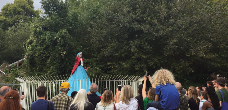 Marcia Farquar is performing on top of the old lido fountain outside Southwark Park Galleries, Lake Gallery. Marcia is wearing a blue bonnet, red open jacket and a blue skirt that flows over the three-tiered semi-circle fountain. In the foreground are lot's of people watching.