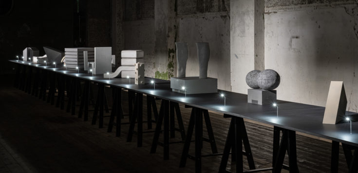 Multiple concrete cultural buildings in a line, lit with small street lights on a black trestle table.⠀